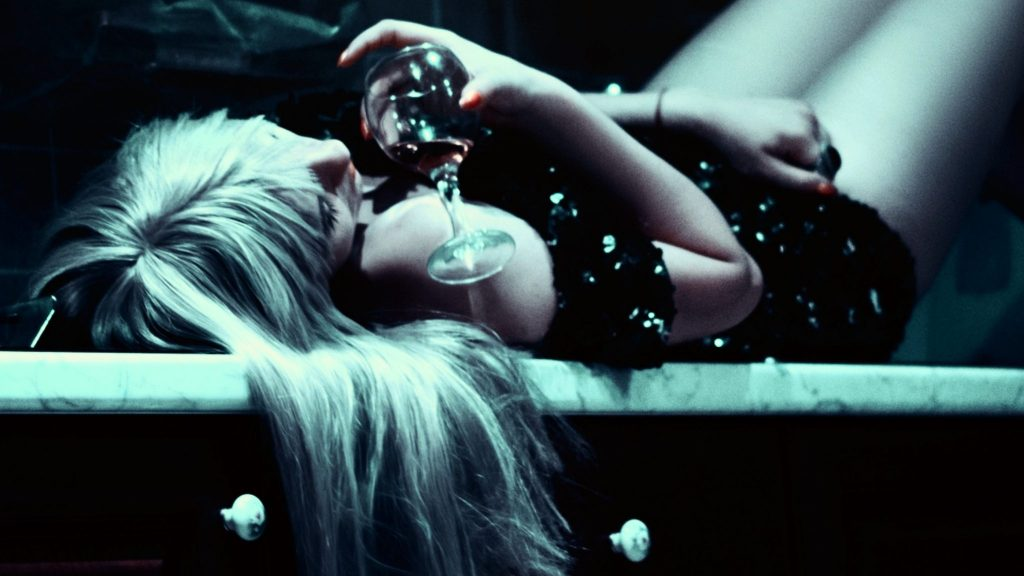 Picture of a woman lying down holding a glass of alcohol