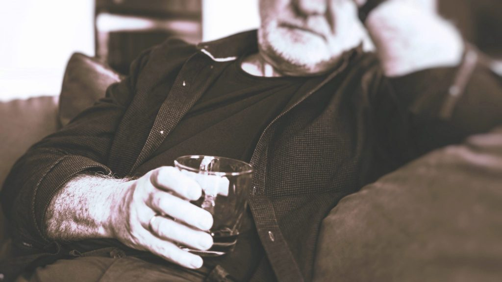 Photo of a seated old guy holding a glass with alcohol