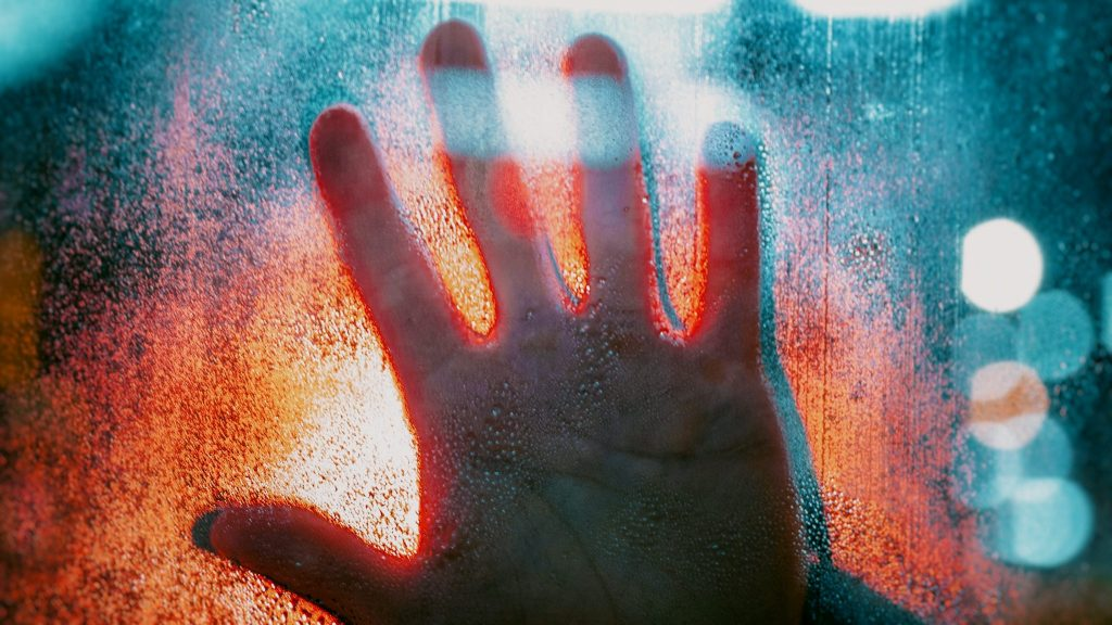 Photo of a hand touching a crystal window
