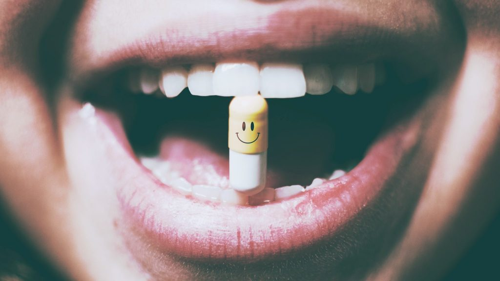 Photo of a person holding a pill with her mouth