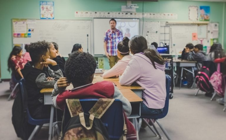 Photo of a classroom full of teenagers being accompanied by their teacher