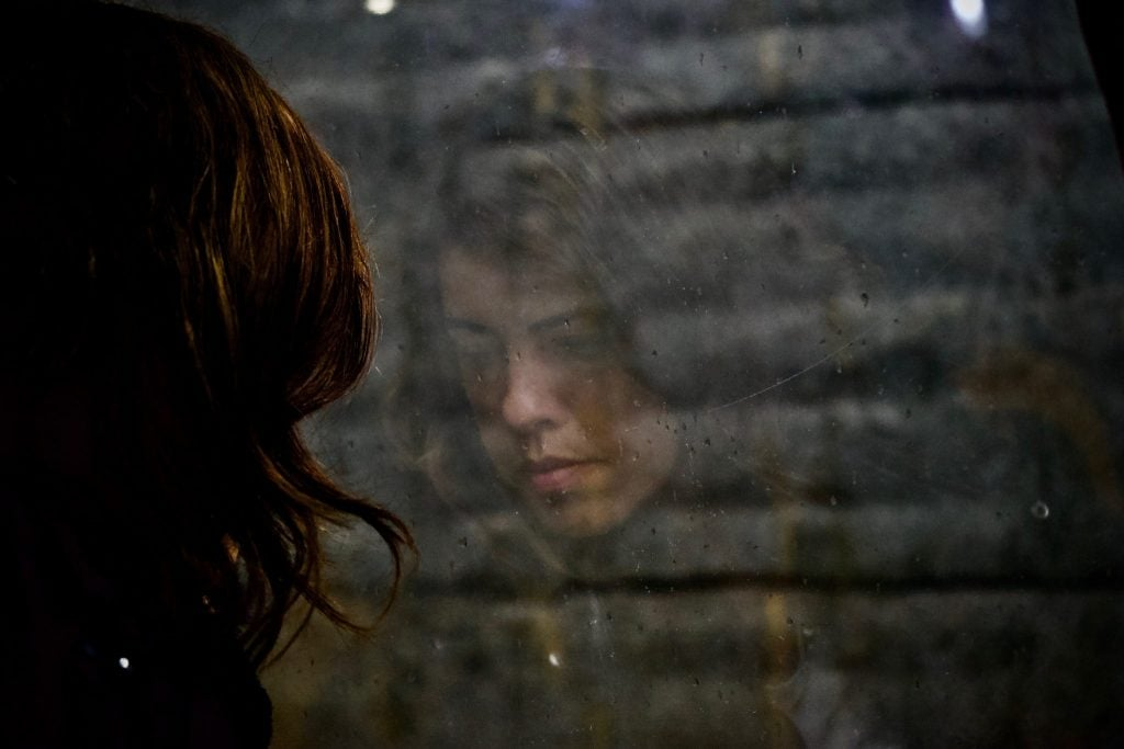 Photo of a sad looking woman thinking while seeing something through a window